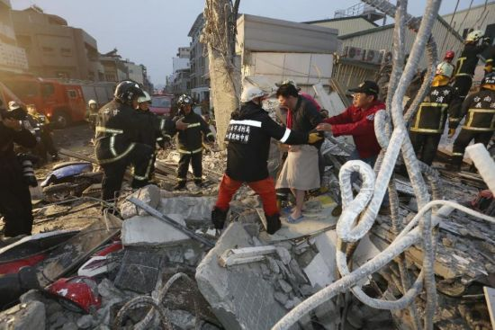 Rescue workers guide a man from the rubble of a toppled building after an earthquake in Tainan, Taiwan, Saturday, Feb. 6, 2016. The 6.4-magnitude earthquake struck southern Taiwan early Saturday, toppling at least one high-rise residential building and trapping people inside. Firefighters rushed to pull out survivors. (AP Photo) TAIWAN OUT