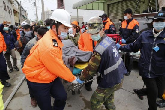 Rescue workers remove a victim on a stretcher from a collapsed building after an earthquake in Tainan, Taiwan, Saturday, Feb. 6, 2016. The powerful, shallow earthquake struck southern Taiwan before dawn Saturday, collapsing a high-rise residential complex. (AP Photo/Wally Santana)