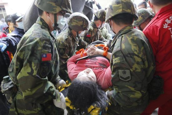 Rescue workers carry a woman on a strecher from a collapsed building after an earthquake in Tainan, Taiwan, Saturday, Feb. 6, 2016. The powerful, shallow earthquake struck southern Taiwan before dawn Saturday, collapsing a high-rise residential complex. (AP Photo/Wally Santana)