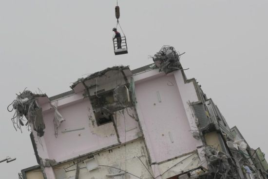 A rescue worker in a bucket hanging from a crane searches a collapsed building from an early morning earthquake in Tainan, Taiwan, Saturday, Feb. 6, 2016. A powerful, shallow earthquake struck southern Taiwan before dawn Saturday. (AP Photo/Wally Santana)