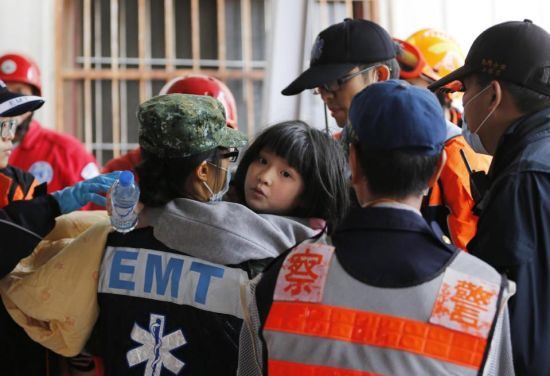 A girl is rescued from a collapsed building in an early morning earthquake in Tainan, Taiwan, Saturday, Feb. 6, 2016. A powerful, shallow earthquake struck southern Taiwan before dawn Saturday. (AP Photo/Wally Santana)