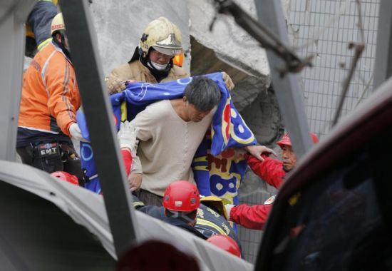 A man is rescued from a collapsed building in an early morning earthquake in Tainan, Taiwan, Saturday, Feb. 6, 2016. A powerful, shallow earthquake struck southern Taiwan before dawn Saturday. (AP Photo/Wally Santana)