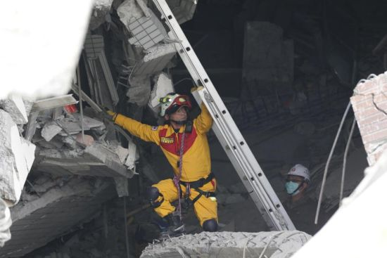 Rescue workers search a collapsed building from an early morning earthquake in Tainan, Taiwan, Saturday, Feb. 6, 2016. A powerful, shallow earthquake struck southern Taiwan before dawn Saturday. (AP Photo/Wally Santana)