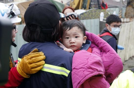 A baby boy is rescued from a collapsed building after an earthquake in Tainan, Taiwan, Saturday, Feb. 6, 2016. A powerful, shallow earthquake struck southern Taiwan before dawn Saturday. (AP Photo/Wally Santana)
