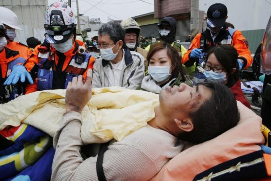 A man is rescued from a collapsed building after an earthquake in Tainan, Taiwan, Saturday, Feb. 6, 2016. A powerful, shallow earthquake struck southern Taiwan before dawn Saturday. (AP Photo/Wally Santana)