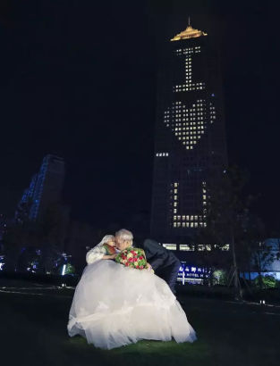 """Qiao Dewei and his wife Liu Shixiu wear wedding clothes to celebrate 67 years of marriage in Xiaoshan District, Hangzhou City, East China's Zhejiang Province, Feb. 14, 2016. A grandson planned the event to celebrate the couple's 67 years of marriage on the Valentine's Day. The grandfather, Qiao Dewei, who is 84, said he neither did anything romantic nor said """"I love you"""" to his wife Liu Shixiu, 83, during their shared life. The grandson worked with a hotel to organize the event. (Photo/Qianjiang Evening News)"""