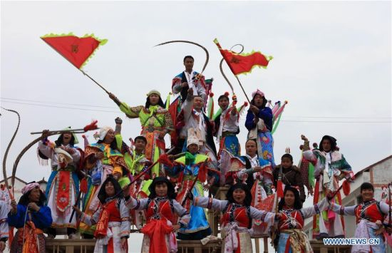 Performers greet the audience after their performance of Gaotai Dixi, a local folk opera staged on the open space of flat land, at Weiqi Village of Puding County, southwest China's Guizhou Province, Feb. 15, 2016. Performers wearing masks stage the opera on 48 tables laid in five layers in shape of pyramid, and sometimes jump down to sing and dance. The Gaotai Dixi opera mainly reflects and tells wartime stories in ancient times. (Photo: Xinhua/Lu Wei)