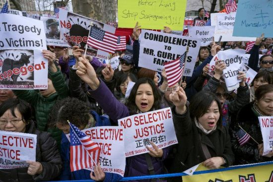 Protesters attend a rally in the Brooklyn borough of New York Saturday, Feb. 20, 2016, in support of a former NYPD police officer Peter Liang, who was convicted of manslaughter for the 2014 shooting death of Akai Gurley, in a housing project stairwell. The 28-year-old Liang, who testified the shooting was an accident, could be sentenced to 5 to 15 years for shooting Gurley, who was unarmed. (AP Photo/Craig Ruttle)
