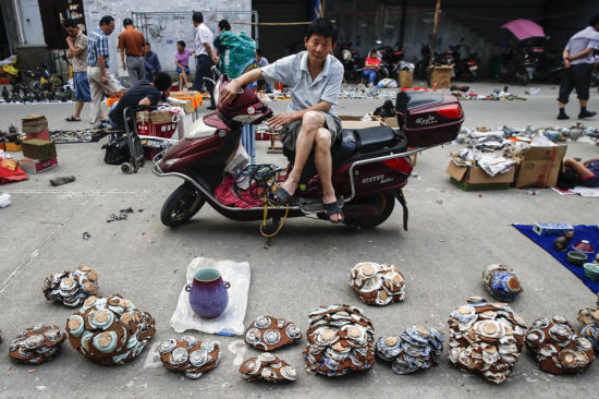 """Jingdezhen homes dozens of ceramic markets, selling all ranges of porcelain and pottery products. Photo shows lumps of """"unearthed"""" porcelains on an old morning fair."""