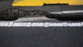 Photo illustration shows cracked asphalt after quake