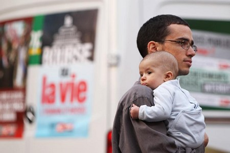 A man and his child attend a protest in Cannes