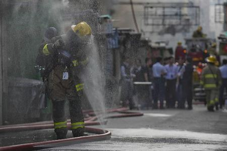 Rescuers work at the site of a fire in downtown Hong Kong